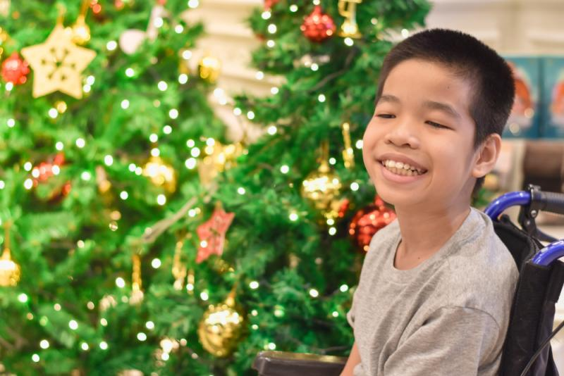 Child in a wheelchair with Christmas tree