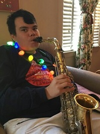 young man playing a trompet with Christmas lights on the neck
